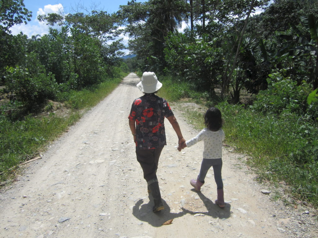 a woman and child walk down a dirt road